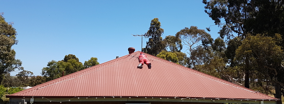 A santa struggling to put up Christmas lights in Kangarilla, Adelaide Hills, South Australia.